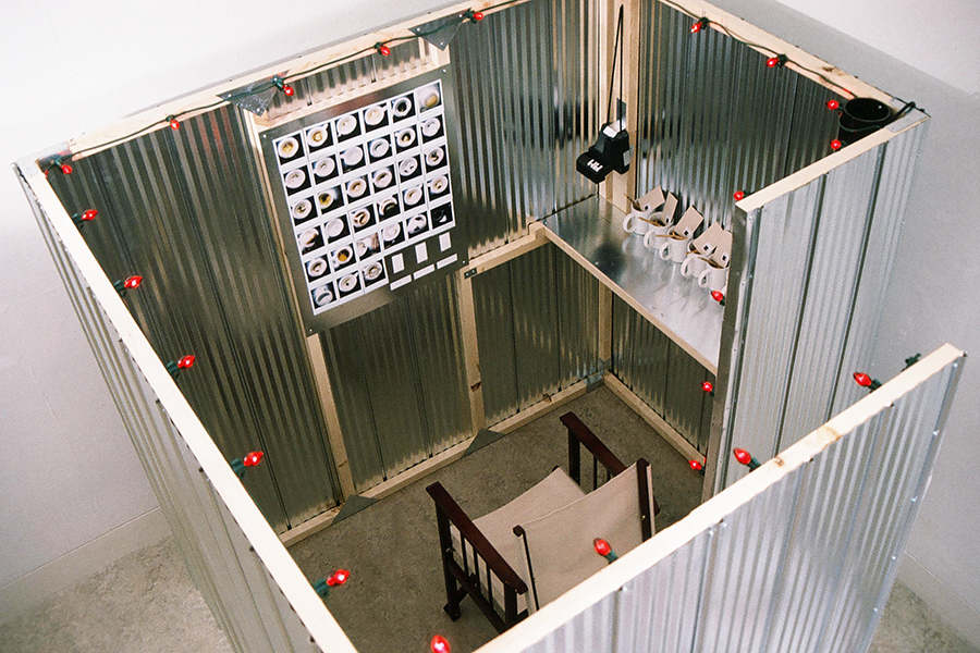 RED STEEL BOX, art installation by Kennedy Telford. The visitor is invited into the box to make a cup of tea, drink it, take a Polaroid photograph of the cup, and post the photograph on the wall.