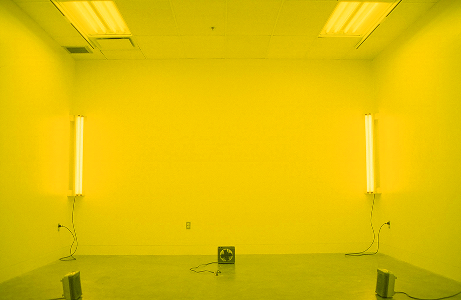 Yellow room image from TOO MUCH IN THE SUN by Kennedy Telford. The lighting in a room is covered in yellow gels and the room is heated to a warm temperature.