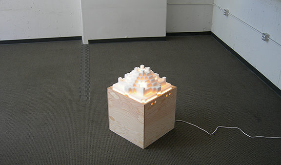 AZIMUTH, a castle-shaped sculpture of sugar cubes resting on a handbuilt wooden box, is lit from within. Work by Kennedy Telford.